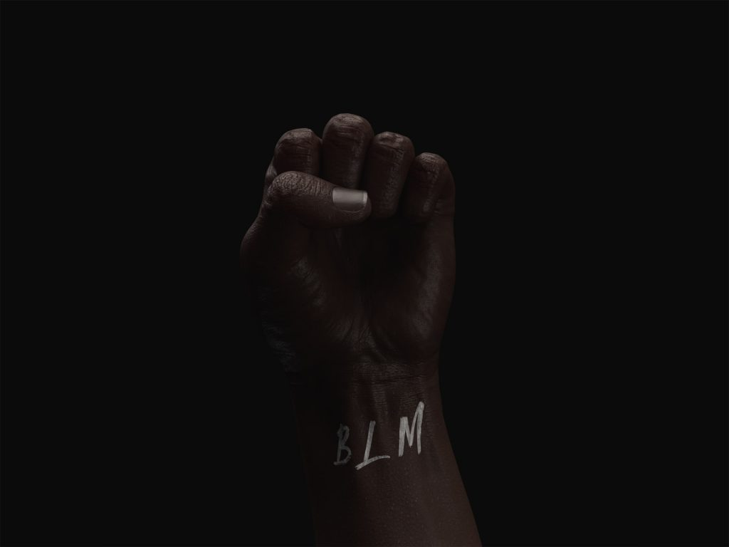 "A Black person's fist raised with the letters ""BLM"" written across the wrist."