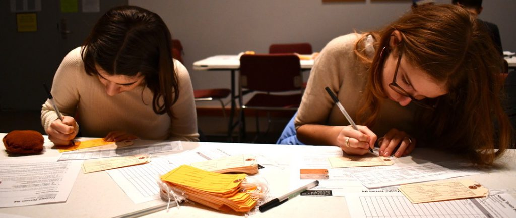 two people leaning closely over a table while filling out toe tags for the HT94 project