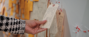 a hand reaching out to hold a filled out toe tag on the HT94 Wall